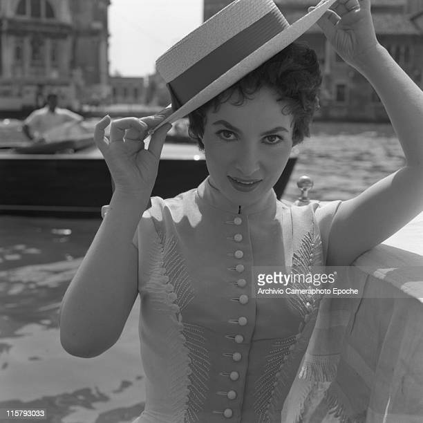 Italian actress Gina Lollobrigida wearing an embroidered dress and a straw hat portrayed in a closeup the Canal Grande behind her Venice 1954