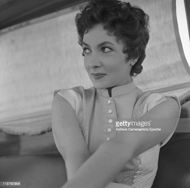 Italian actress Gina Lollobrigida wearing an embroidered dress portrayed from below her arms crossed Venice 1954