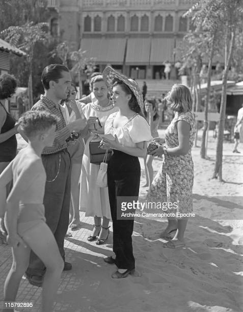 Italian actress Gina Lollobrigida with a wide brimmed straw hat holding a handbag and talking to a fan Carlo Giovetti asking for an autograph in...