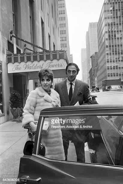 Italian actress Gina Lollobrigida with her current partner American businessman George Kaufmann getting on a car after their stay at WaldorfAstoria...