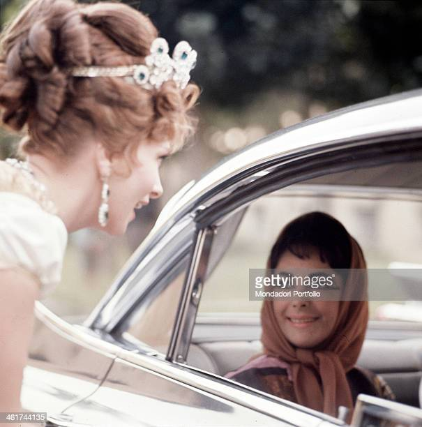 Italian actress Gina Lollobrigida with her hair bunched up and the forehead encircled by a diadem greets the American diva Elizabeth Taylor her head...