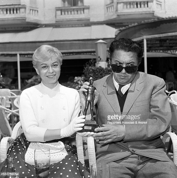 Italian actress Giulietta Masina and Italian director Federico Fellini showing the award they won for the film La Strada 1956