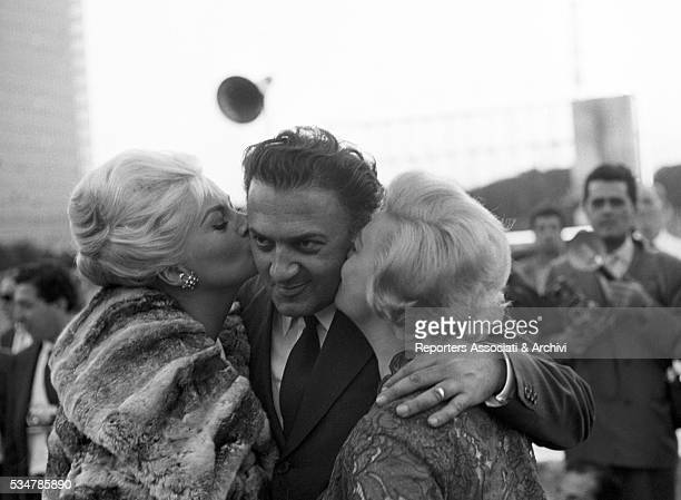 Italian actress Giulietta Masina and Swedishborn Italian actress Anita Ekberg kissing Italian director Federico Fellini at the press conference for...
