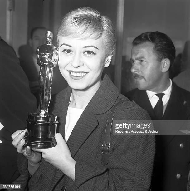 Italian actress Giulietta Masina arriving from New York at Ciampino Airport and holding the Academy Award that she won for the film Nights of Cabiria...