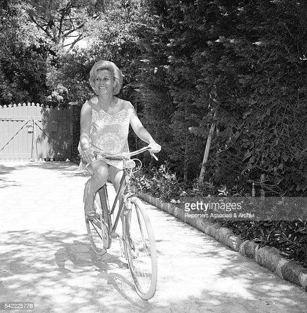 Italian actress Giulietta Masina cycling in the streets of Fregene Fregene 1956