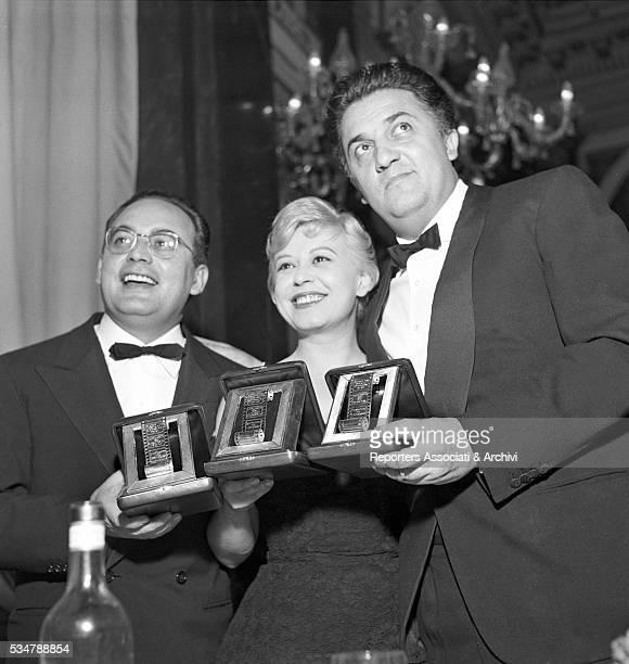 Italian actress Giulietta Masina Italian director Federico Fellini and Italian film producer Dino De Laurentiis attending the Nastri d'Argento...