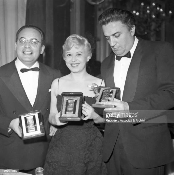 Italian actress Giulietta Masina Italian director Federico Fellini and Italian producer Dino De Laurentiis at the Silver Ribbon award ceremony at the...