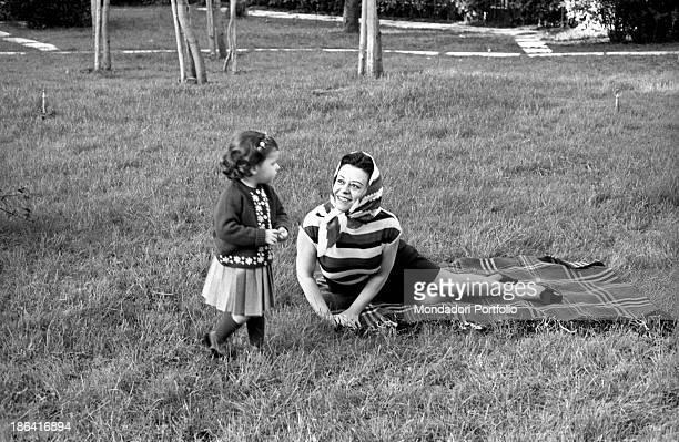 Italian actress Giulietta Masina playing in the garden of her house in Fregene with her niece Francesca Fabbri, daughter of Maria Maddalena Fellini....