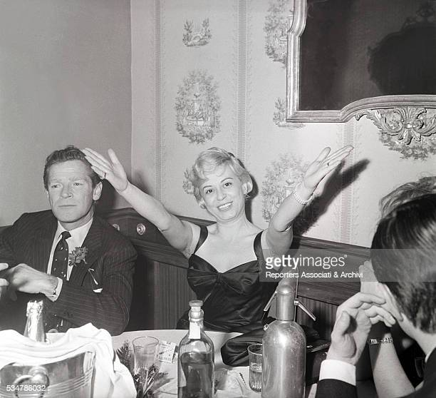 Italian actress Giulietta Masina with open arms and American actor Richard Basehart sitting at the table 1958