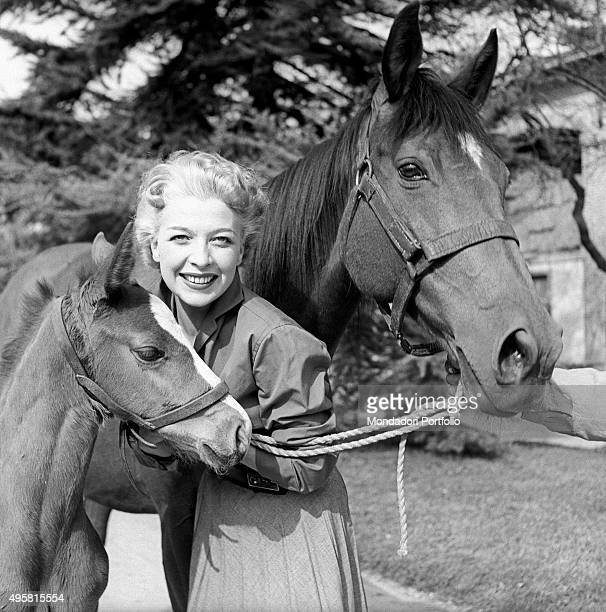 Italian actress Isa Barzizza poses smiling between a horse and a colt discovered by the histrionic Erminio Macario brang to fruition of the audience...