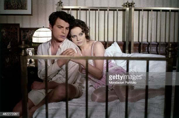 Italian actress Laura Antonelli and Italian actor and director Michele Placido hugging sitting together on a double bed in the film The Divine Nymph...
