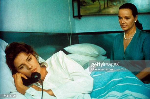Italian actress Laura Antonelli assisting American actress Tahnee Welch lying in a hospital bed with a telephone in her hand in the TV series...