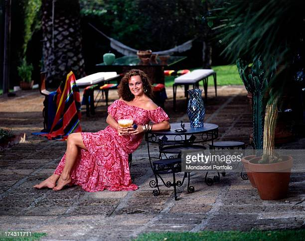 Italian actress Laura Antonelli sitting in a garden leaning on a table Italy 1989
