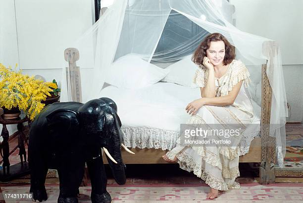 Italian actress Laura Antonelli sitting on a fourposter bed in front of a stone elephant Italy 1990
