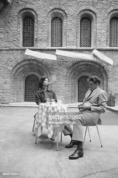 Italian actress Lea Massari and Italian actor and basket player Enrico Pagani smoking at a cafè table during the XVIII Venice International Film...