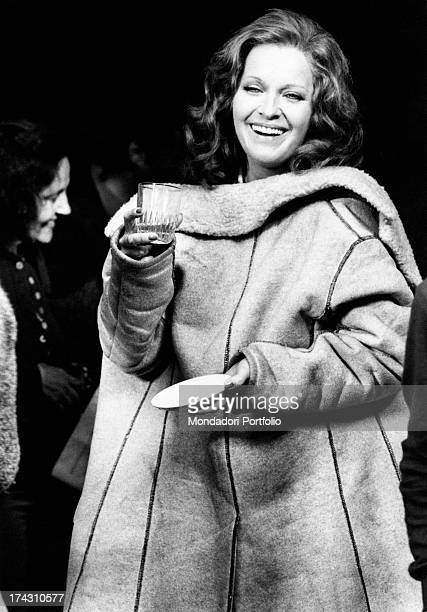 Italian actress Lisa Gastoni holding a glass and smiling on the set of the film Bitter Love Ferrara 1974