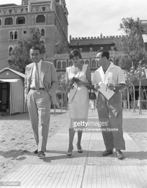 Italian actress Lucia Bosè, wearing a dress and holding a camera, walking out of the Excelsior Hotel with Stefano Carretta and Franco Villani, Lido,...