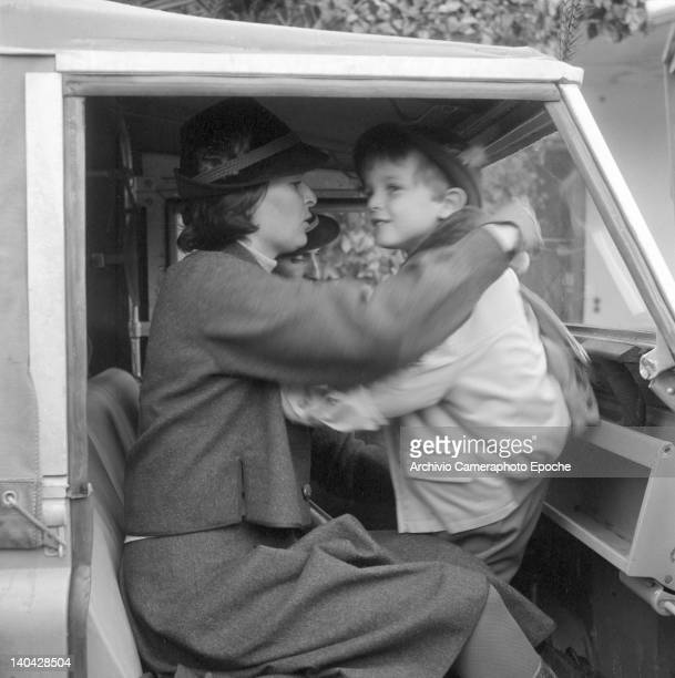 Italian actress Lucia Bose dressing up Miguel Bose in a car, Madrid, 1961.