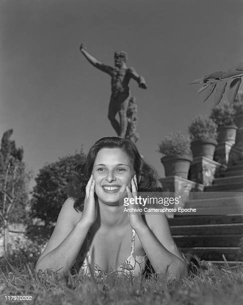 Italian actress Lucia Bose portrayed lying on the grass, wearing a floral dress, a statue on the background, during the pageant Miss Italia, Stresa...