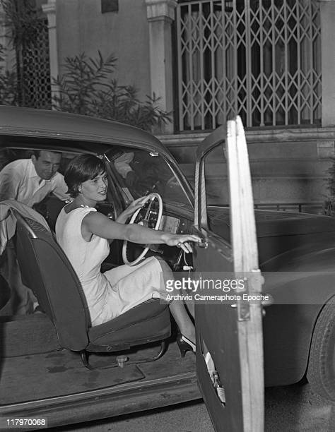 Italian actress Lucia Bose, wearing a sleeveless dress, portrayed while closing her car door, a man entering from the passenger side, Venice, Movie...