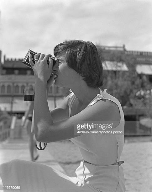 Italian actress Lucia Bose wearing a sleeveless dress portrayed while shooting with a camera outside the Excelsior Hotel during the Movie Festival...