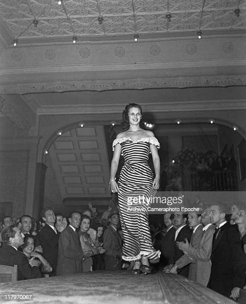 Italian actress Lucia Bose, wearing a striped naked-shoulder dress, modelling on a runway, the public applauding beneath, Venice 1947.