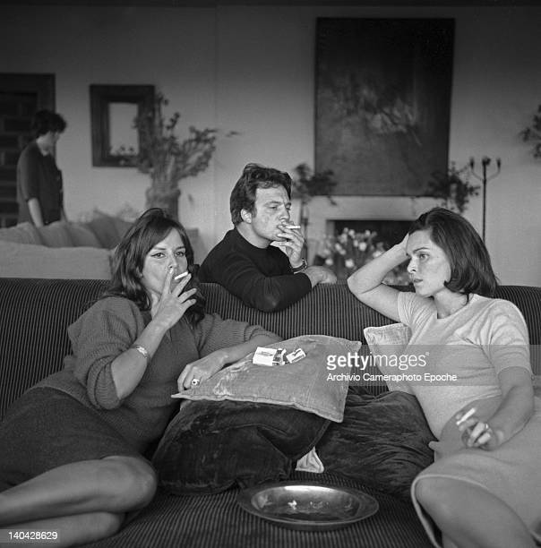 Italian actress Lucia Bose with Franco Interlenghi and Antonella Lualdi sitting on a sofa and smoking a cigarette Madrid 1961