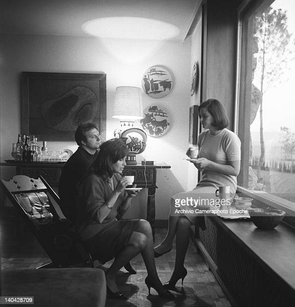 Italian actress Lucia Bose with Franco Interlenghi and Antonella Lualdi sitting beside the window sipping a cup of tea, Madrid, 1961.