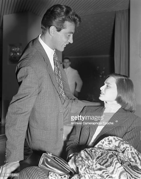Italian actress Lucia Bose with her partner Walter Chiari, sitting and chatting in an hotel hall in Venice, 1947. She is wearing a pinstriped...