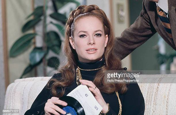 Italian actress Luciana Paluzzi pictured holding a 45rpm single record in a scene from the film 'A Black Veil for Lisa' in Italy in March 1968