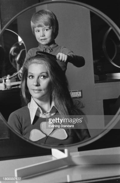 Italian actress Luisa Mattioli, the wife of actor Roger Moore, has her hair combed by a little boy, UK, 14th February 1972.