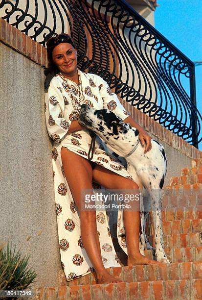 Italian actress Lydia Alfonsi in beach robe hugging a big spotted dog 1971