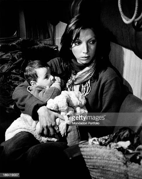 Italian actress Mariangela Melato sitting on a train carriage holding a baby in the film Caro Michele Italy 1975
