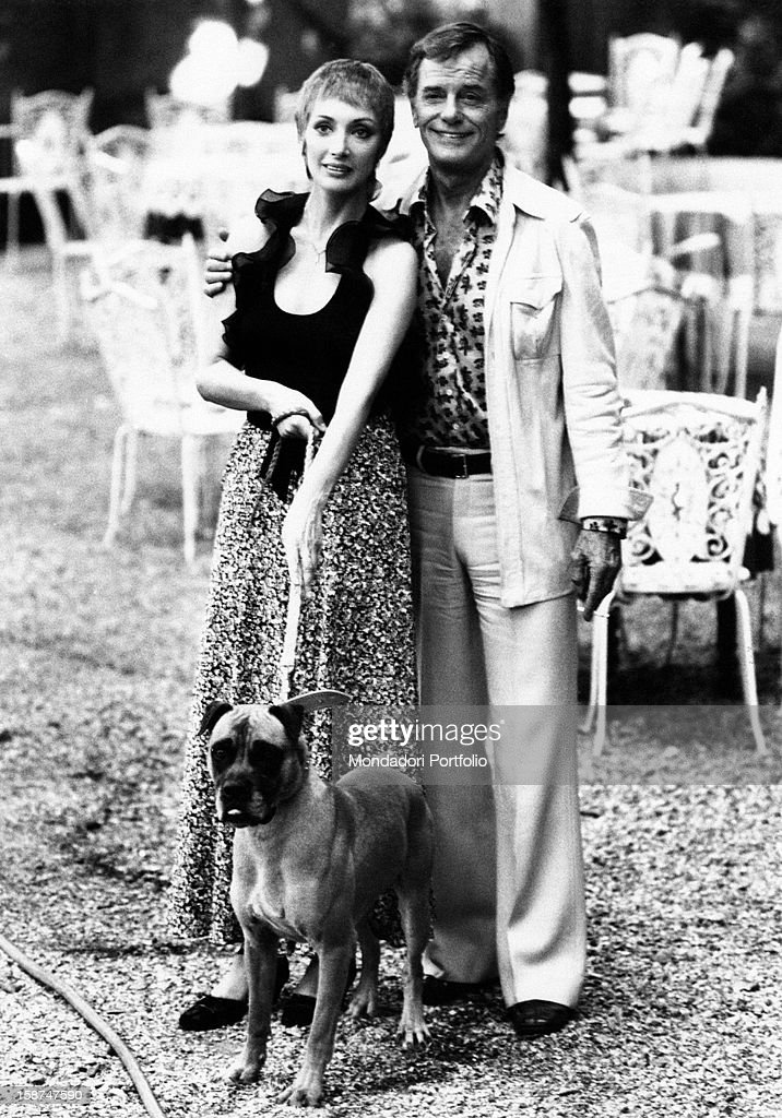 Italian actress Marina Malfatti and American actor Gig Young (Byron Elsworth Barr) posing with a dog on the set of the film A Black Ribbon for Deborah. Rome, 1974