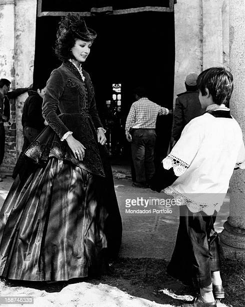 Italian actress Marina Malfatti wearing a stage costume and talking to an altar boy on the set of the film Malombra Belgirate 1974