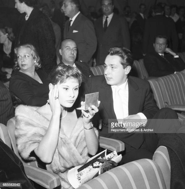 Italian actress Marisa Allasio adjusting her makeup with a mirror at the premier of the show L'adorabile Giulio at Teatro Sistina Sitting next to her...