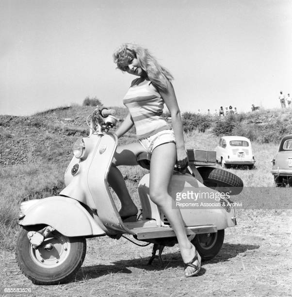 Italian actress Marisa Allasio posing seated onto a Vespa during a break on the set of the film 'The Sword and the Cross' Rome 1956