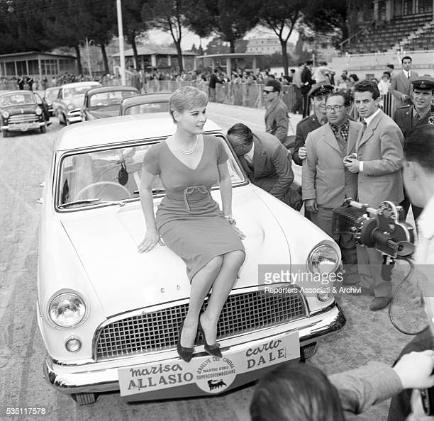 Italian actress Marisa Allasio posing sitting on a car bonnet at the 4th Cinema Rally Sanremo April 1957