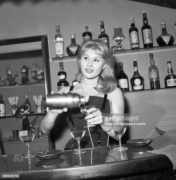 Italian actress Marisa Allasio preparing a cocktail in the famous Roman club Kit Kat for the election party of Miss Cocktail. Rome, 1957