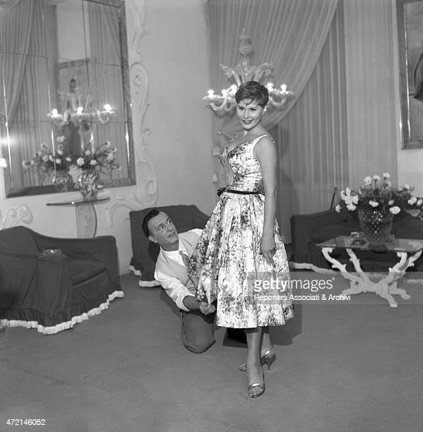 Italian actress Marisa Allasio trying on a dress at Italian tailor Emilio Federico Schubert's atelier He tidies the hem Rome 1958