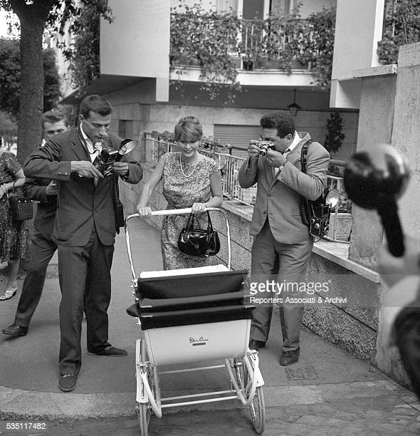 Italian actress Marisa Allasio walking with her son Carlo Giorgio Calvi in the pram surrounded by photographers 1st August 1959
