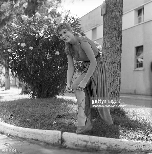 Italian actress Marisa Allasio wearing a stage costume and adjusting her sandal during a break in the boulevards of Cinecittà Rome 1956