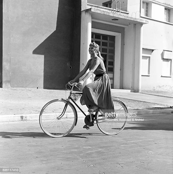 Italian actress Marisa Allasio wearing a stage costume and riding a bicycle during a break in the boulevards of Cinecittà Rome 1956