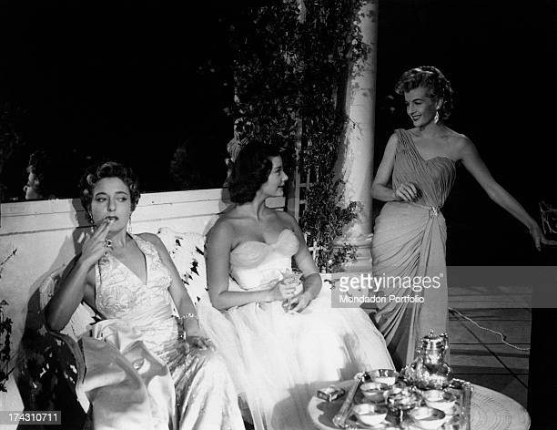 Italian actress Miriam di San Servolo smoking Italian actress Lyla Rocco and Frenchborn American actress Corrine Calvet smiling at each other in One...