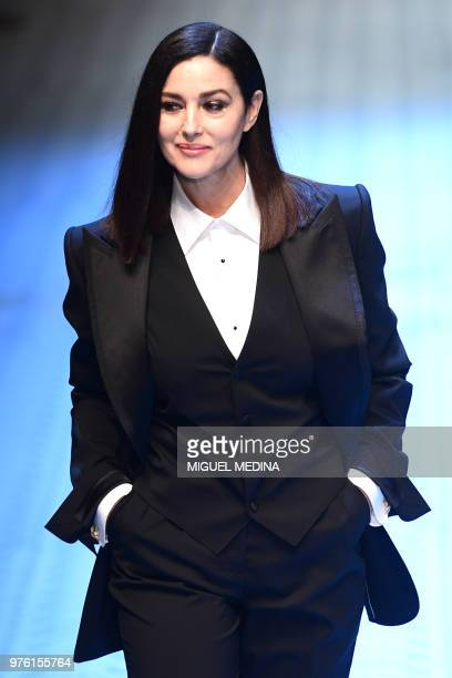 Italian actress Monica Bellucci presents a creation by Dolce Gabbana during the women's spring/summer 2019 collection fashion show in Milan on June...
