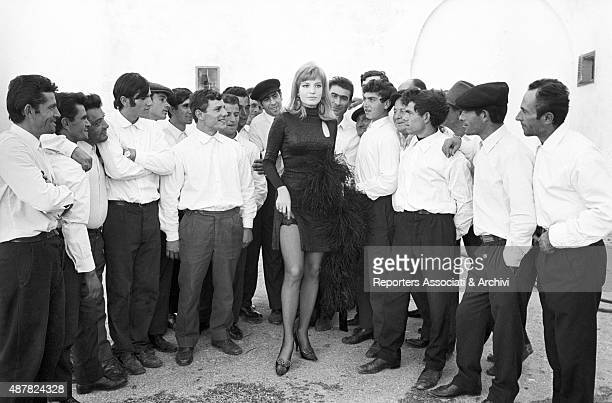 Italian actress Monica Vitti surrounded by extras in the film The Girl with a Pistol 1968