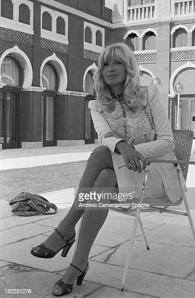 Italian actress Monica Vitti wearing an embroidered tailleur holding sunglasses and sitting on a chair Venice 1980