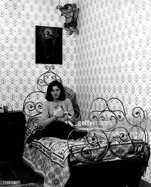 Italian actress Paola Gassman sitting on the bed and hugging a cat Rome January 1963