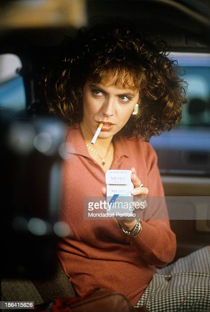 Italian actress Paola Onofri sitting in a car holding a pack of Merit cigarettes in her hand in the film Casa mia casa mia Italy 1988