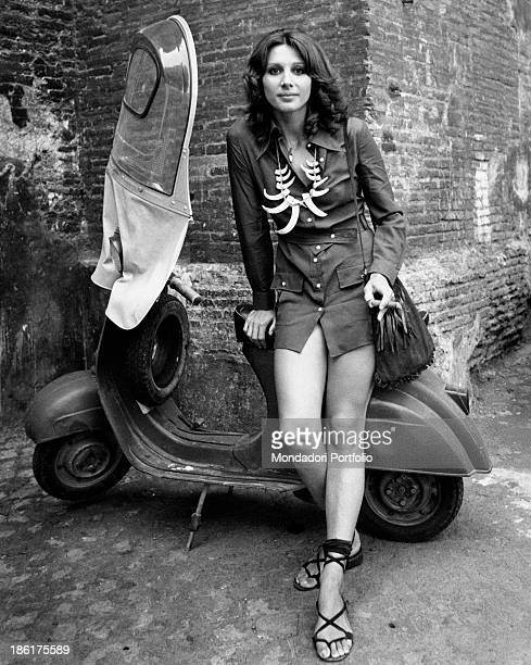Italian actress Paola Pitagora leaning against a Vespa scooter with a cigar between her fingers The actress wears a necklace made of fangs Rome 1970s